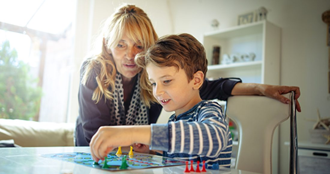 A foster parent plays a board game with a child in foster care.