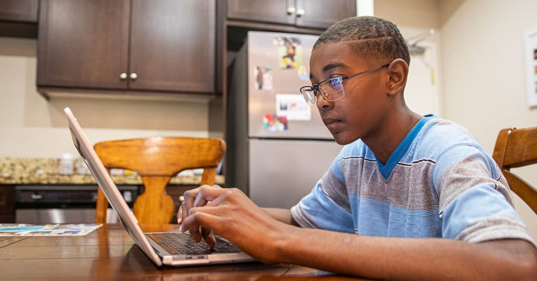 Young person attending school from home during social distancing.