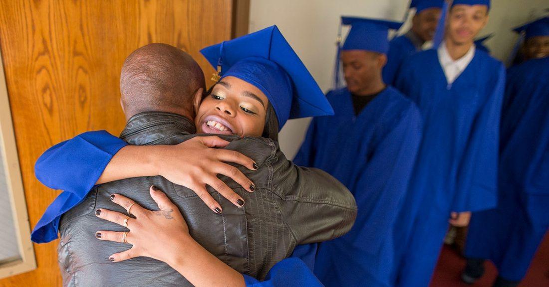 High school graduate greets a family member