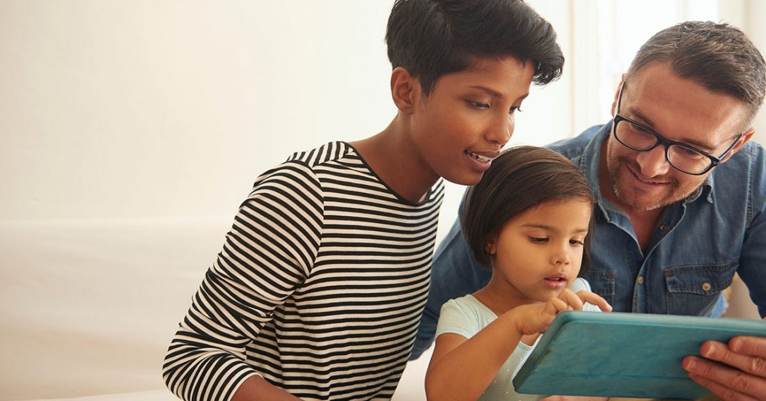 Mother and father look at a tablet with their child