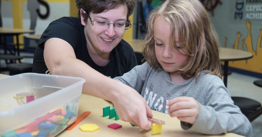 Classroom worker helps a child