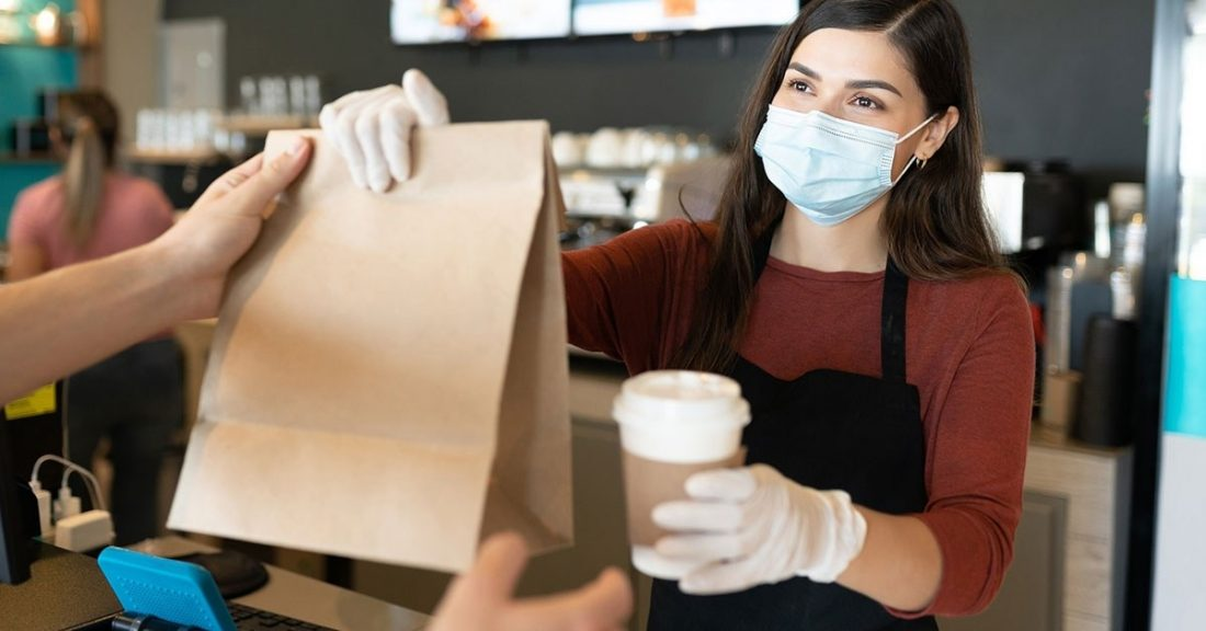 A young female worker at a coffee shop hands a customer their order.