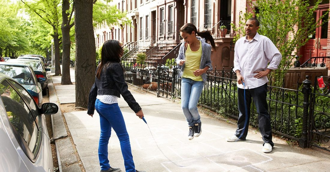 Children and dad playing jump rope in their neighborhood