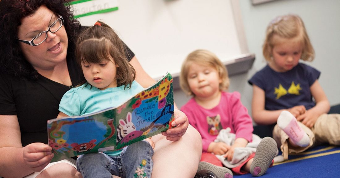 Woman reads to child in a day-care setting.