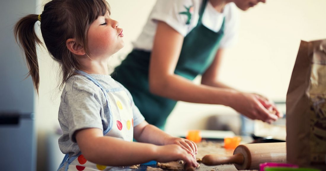 Young parent bakes with child