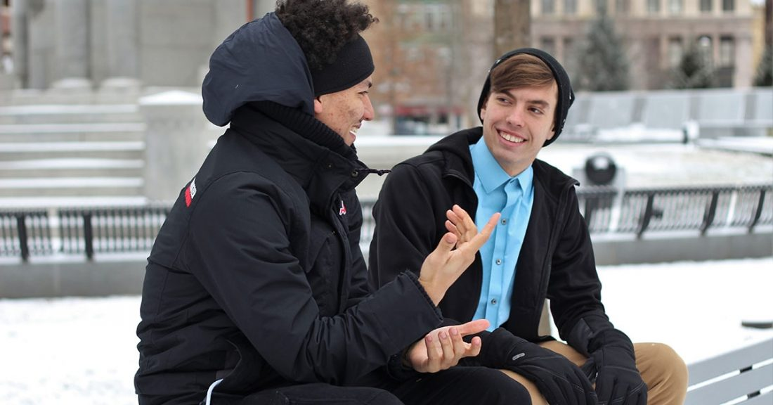 Two young men sitting on a bench in a park