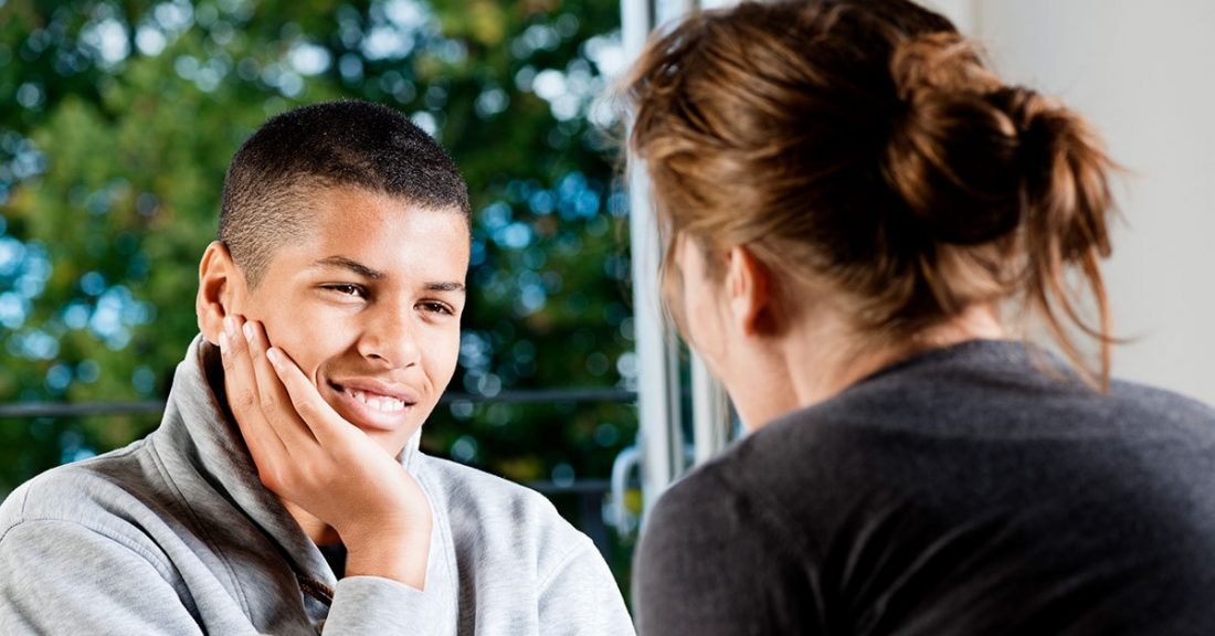 Young person talking with a supportive teacher