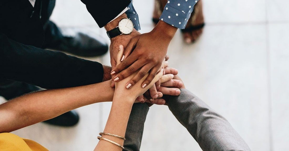 A multiracial group of young people form a circle, each putting a hand in the middle--one on top of the other.