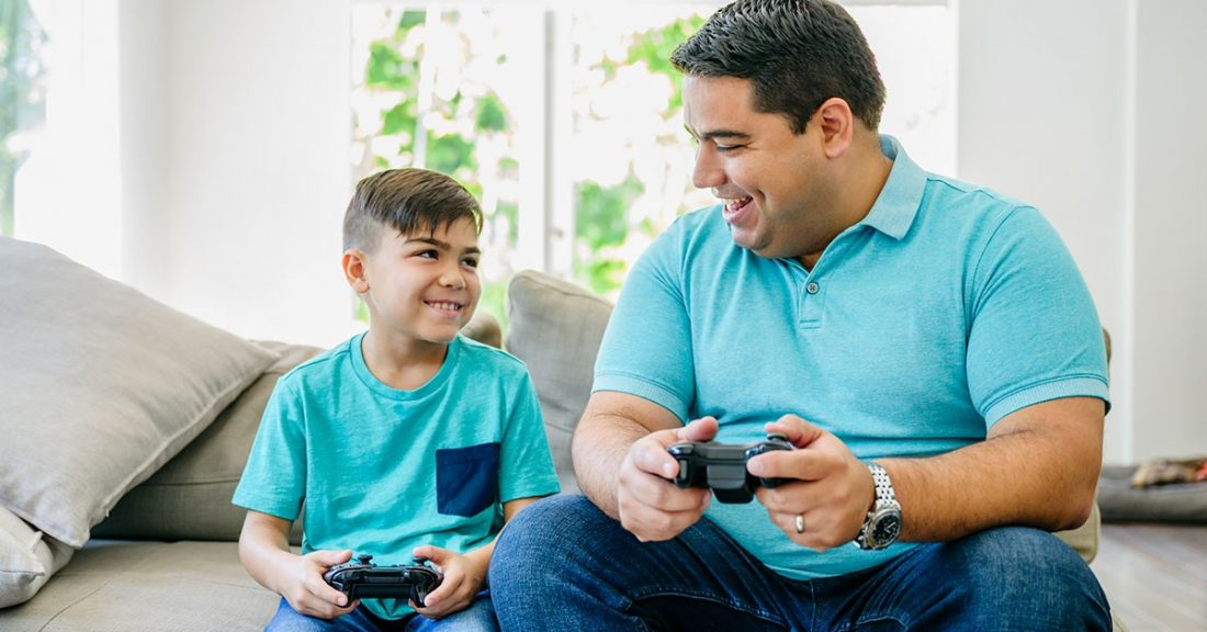 Hispanic male sits with son playing video games