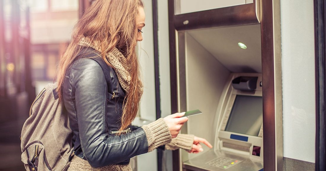 Young woman at ATM machine.