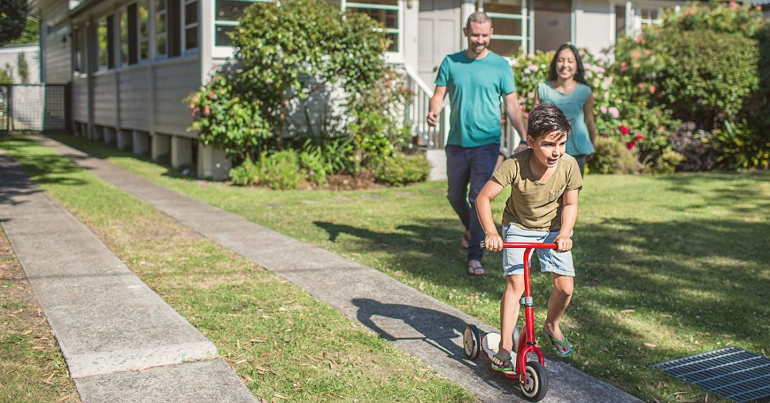 Parents with a young person on a bicycle.