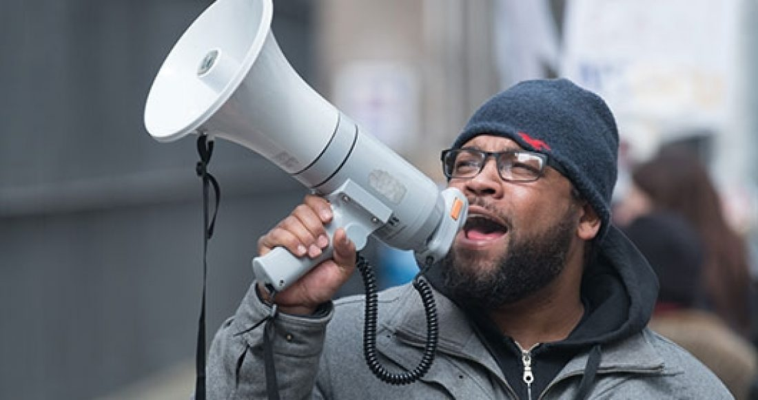 Man at protest speaks into megaphone.