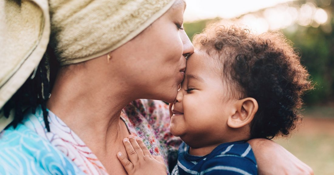 A mom gives her infant a kiss on the forehead.