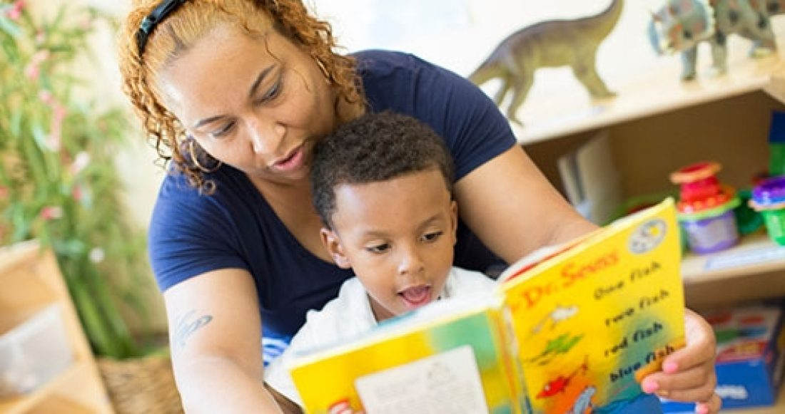 Child care worker and child reading together