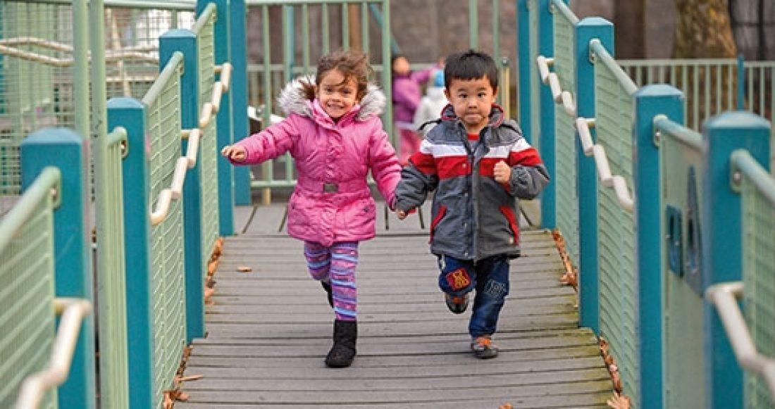 Two children run on a playground