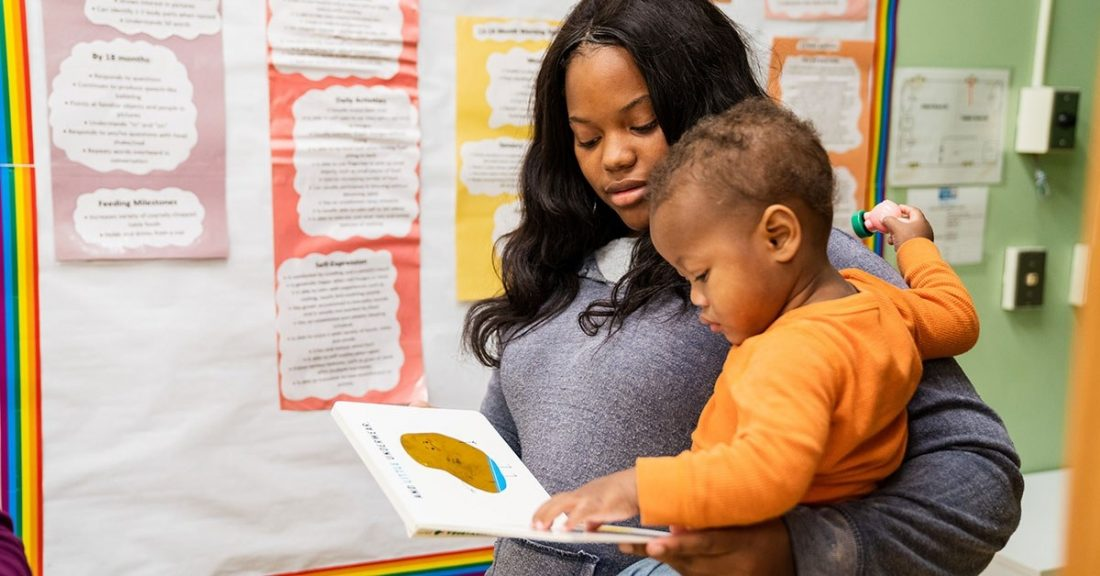 Mom holds baby in classroom setting