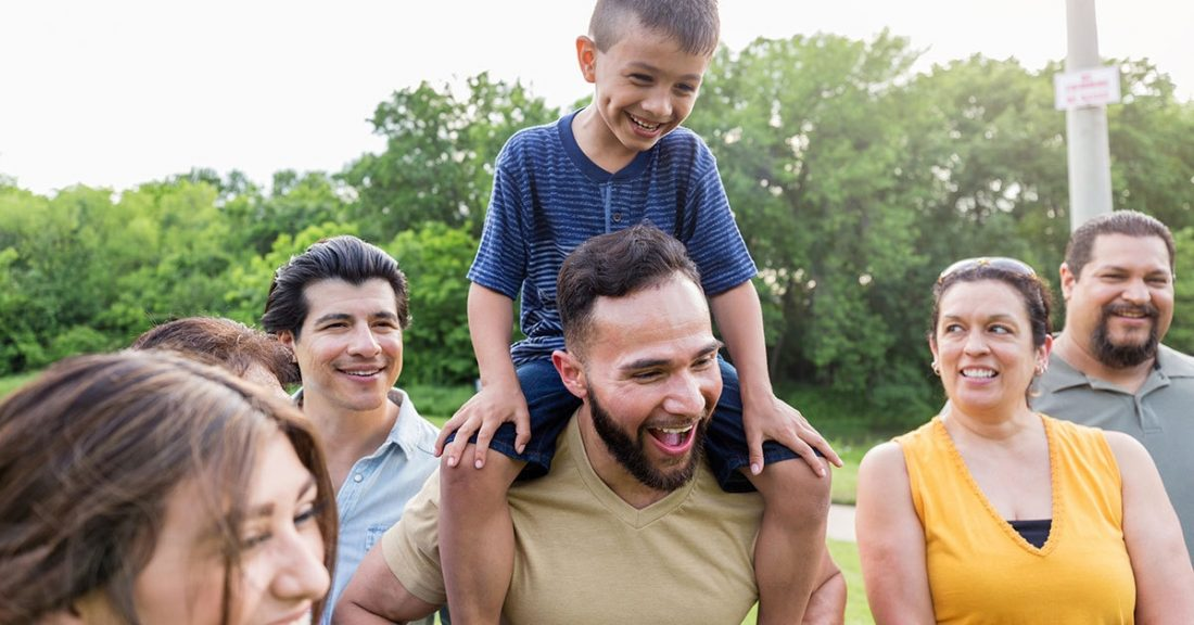 Child on adult's shoulders surrounded by family members