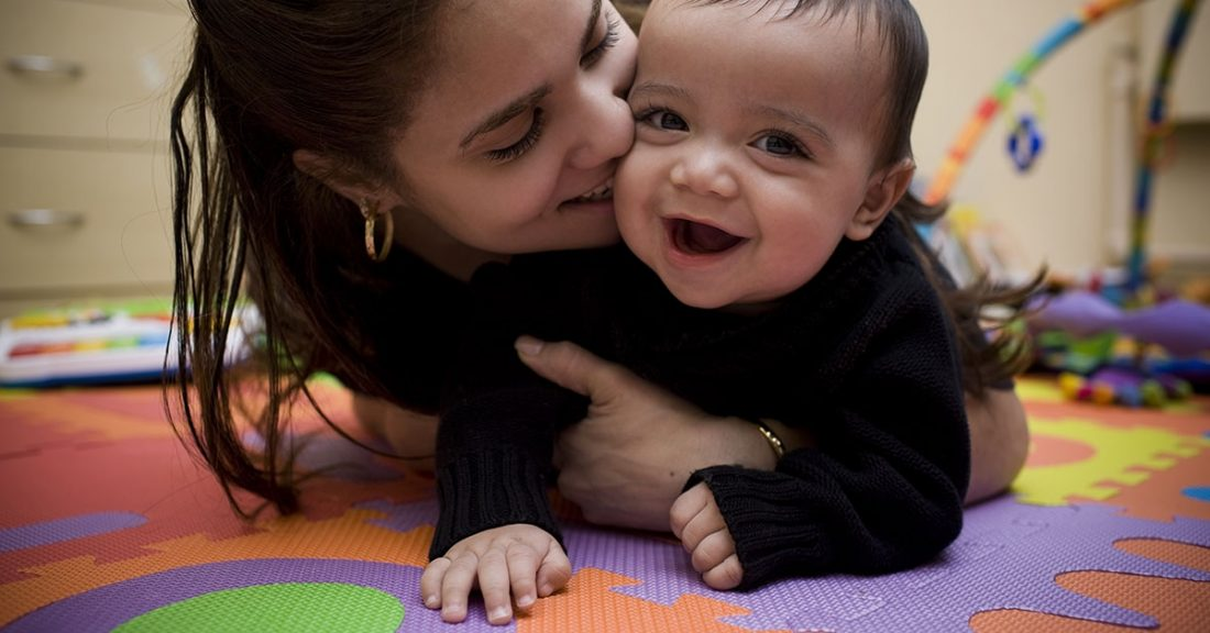 Young mother holding her smiling baby