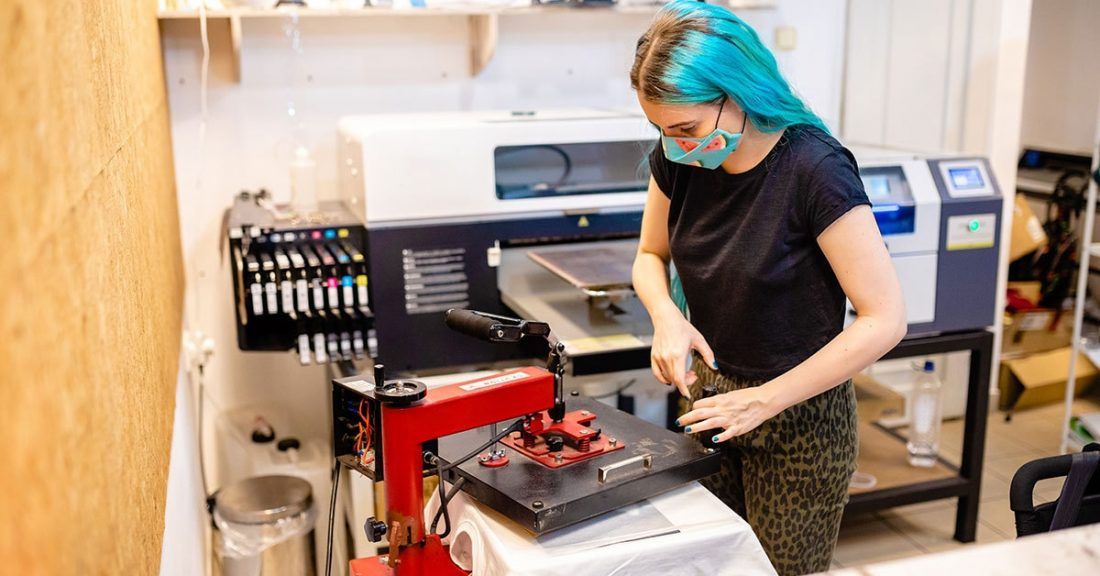 Young person learns how to use a machine through an apprenticeship program