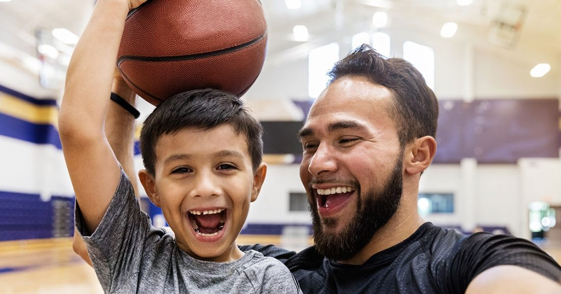 Young father spends time playing basketball with son