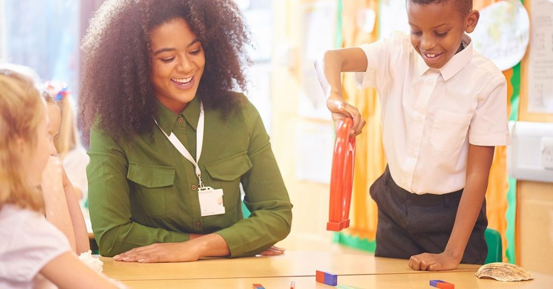 A Black female teacher with textured hair smiles and engages with one young Black student and one young white student.