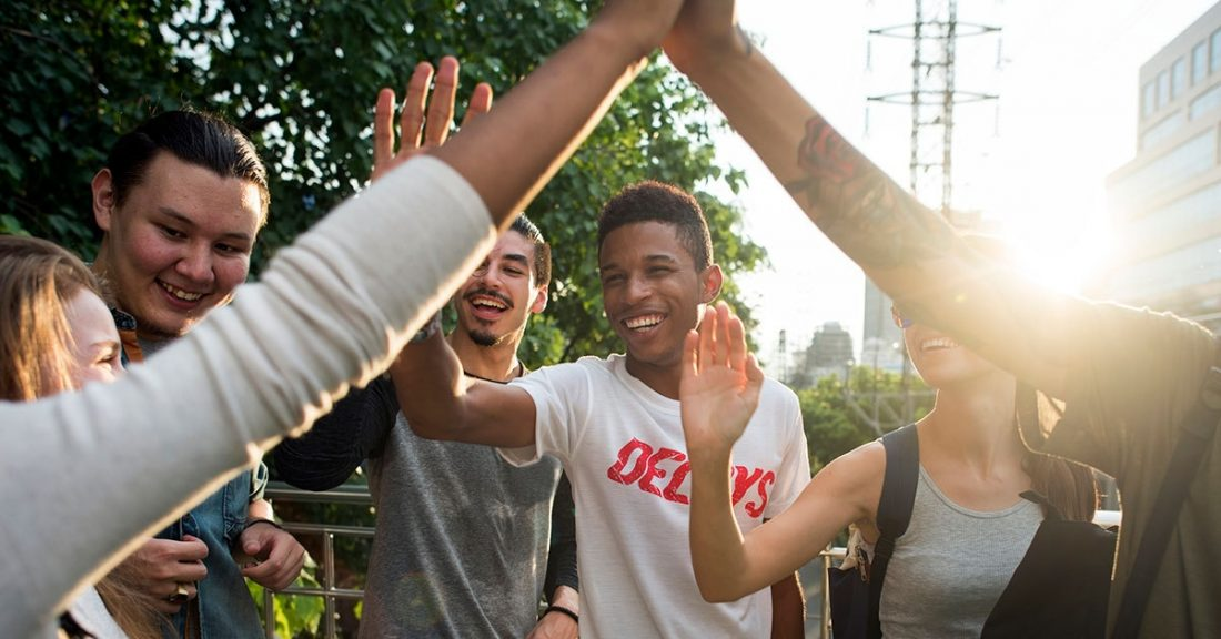 """Group of young people giving each other a """"high five."""""""