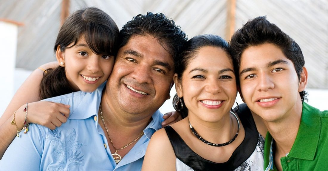 A Latino family of four, including an older boy and younger girl, smile at the camera.