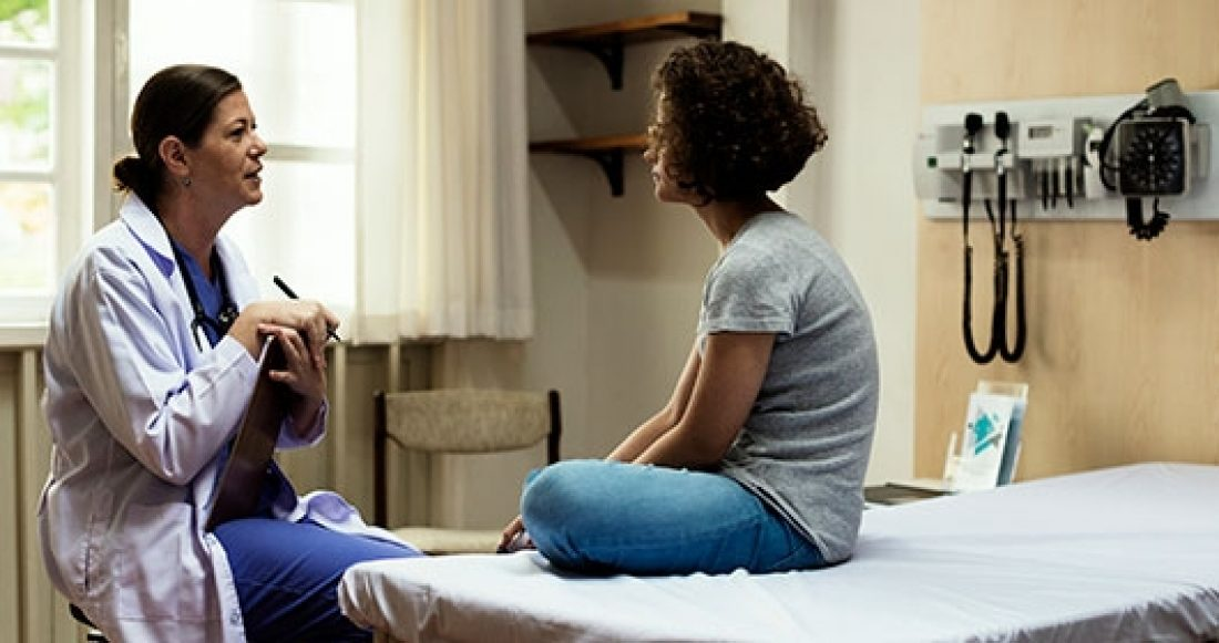 Parent meets with doctor. Parental health insurance helps support family stability.