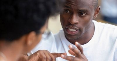 A Black mentor offers advice to a young man.