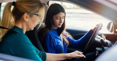 A young girl in a blue shirt and long dark hair sits behind the wheel of a vehicle. An older woman sits next to her and appears to be helping the girl learn how to drive.