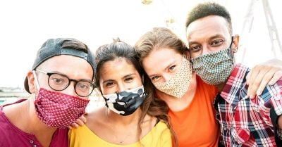 Four young people of different races smile at the camera while wearing masks.