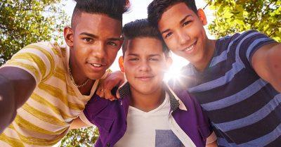 Three teens looking down at camera with sun shining through