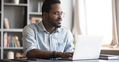Black man with glasses sits inside at a desk, looking at his laptop screen.