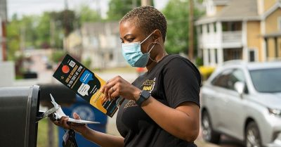 Community member holds pamphlets about reducing violence
