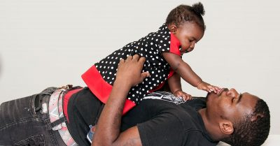 Daughter plays with father on the floor
