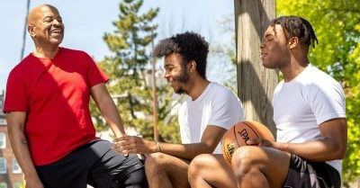 Older Black male talks with two young people outside