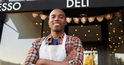 Black man wearing a white apron stands outside a food shop with his arms crossed across his chest.