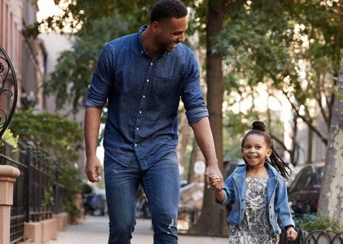 African American father with young daughter walking on city street
