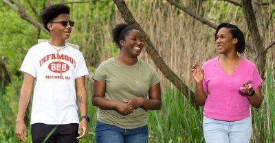 Two Black teens walk alongside an adult woman