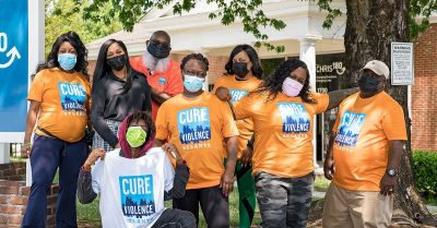 """Group of community members wearing """"Cure Violence"""" t-shirts"""